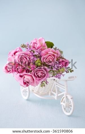 Lilacs and pink roses flowers in a decorative white wooden bicycle on a blue background .Floral gift for a wedding or birthday. #361590806