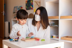 Liltle Preschooler Kid playing wood puzzle with teacher educador help using face mask for coronavirus pandemic. Homeshooling. Learning Community. Montessori School