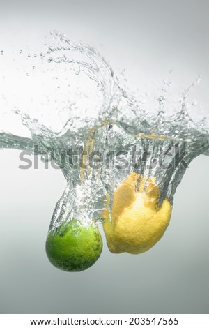 Lime and lemon falling into the water with splash and little air bubbles