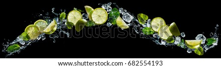 Lime and lemon pieces with mint and ice in water splash #682554193