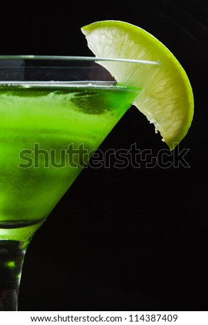 Lime and melon martini cocktail detail on black background