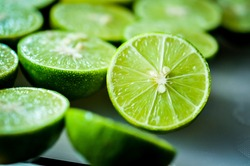 lime Backgrounds, Close up shot, fruit macro photography, Close up sliced of the green limes and seed with a knife place on plastic board in a kitchen. Lime is a kind of fruit. The result is very sour
