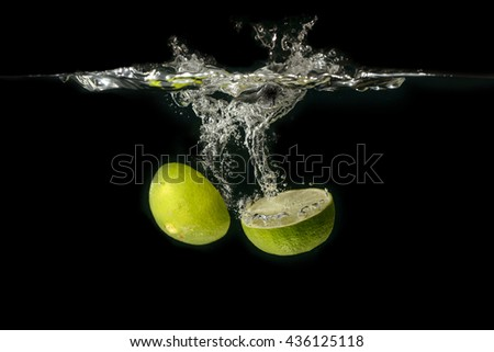 Stock Photo Lime falling into water on black background