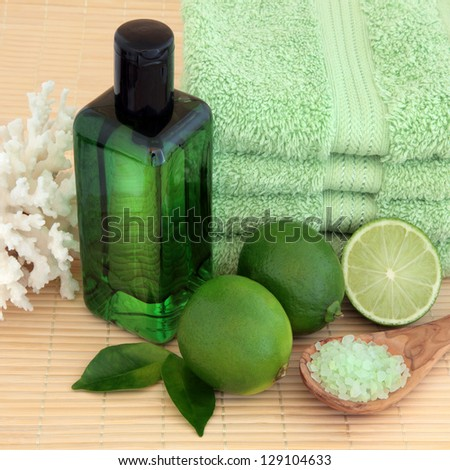 Lime fruit with spa accessories of green towels, bubble bath, sea salt and coral shell over bamboo background.