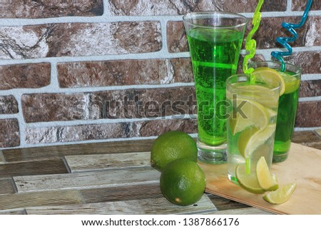 Lime in glass goblets and fruit with mint on a wooden table. Cool refreshments on a hot day, diet food in the summer #1387866176