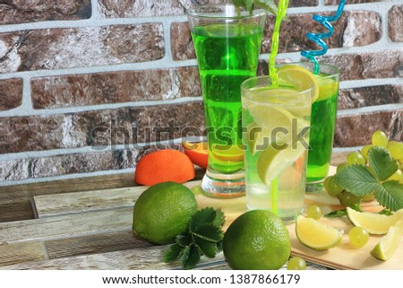 Lime in glass goblets and fruit with mint on a wooden table. Cool refreshments on a hot day, diet food in the summer #1387866179
