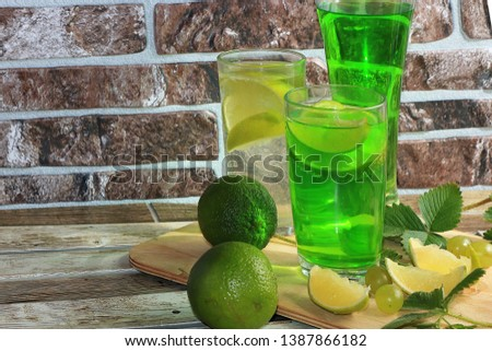 Lime in glass goblets and fruit with mint on a wooden table. Cool refreshments on a hot day, diet food in the summer #1387866182