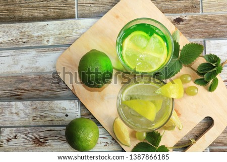 Lime in glass goblets and fruit with mint on a wooden table. Cool refreshments on a hot day, diet food in the summer #1387866185