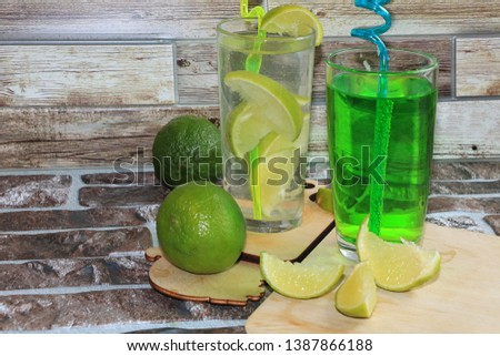 Lime in glass goblets and fruit with mint on a wooden table. Cool refreshments on a hot day, diet food in the summer #1387866188