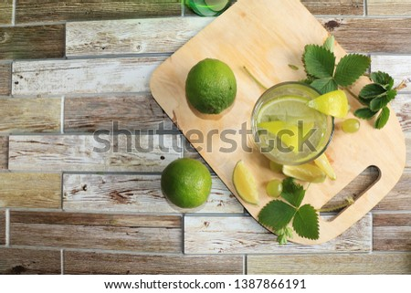 Lime in glass goblets and fruit with mint on a wooden table. Cool refreshments on a hot day, diet food in the summer #1387866191