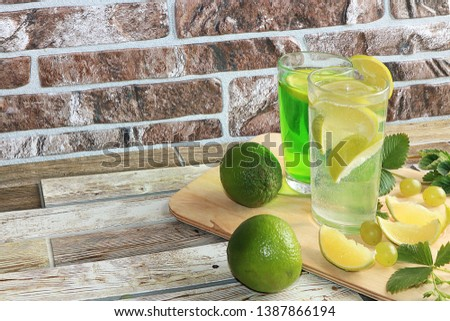 Lime in glass goblets and fruit with mint on a wooden table. Cool refreshments on a hot day, diet food in the summer #1387866194