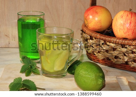 Lime in glass goblets and fruit with mint on a wooden table. Cool refreshments on a hot day, diet food in the summer #1388599460