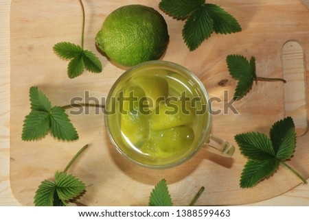 Lime in glass goblets and fruit with mint on a wooden table. Cool refreshments on a hot day, diet food in the summer #1388599463