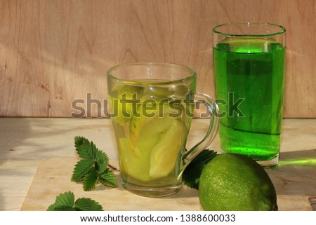 Lime in glass goblets and fruit with mint on a wooden table. Cool refreshments on a hot day, diet food in the summer #1388600033