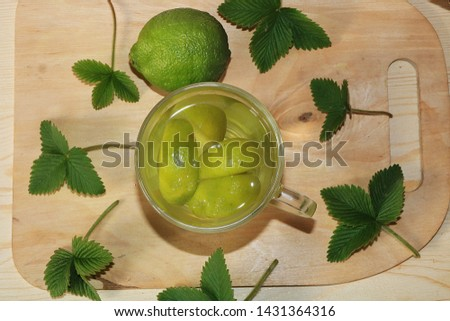 Lime in glass goblets and fruit with mint on a wooden table. Cool refreshments on a hot day, diet food in the summer #1431364316