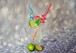 Lime juice with ice in a tall glass with tubules and a cocktail umbrella, ripe citrus fruits nearby on a gray shiny background. Close-up.