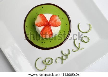Lime parfait topped with fresh strawberries over green lime sauce. - stock photo