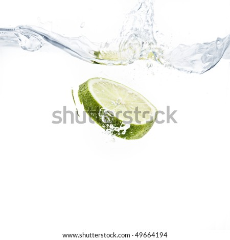 lime slice splashing into water with white background