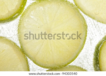 Lime slices in ice closeup photo