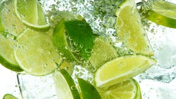 Lime Slices with ice cubes falling deeply under water isolated on white background