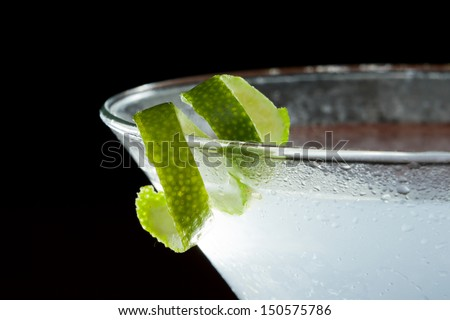 lime twist on the rim of a martini glass used as a garnish isolated on a black background
