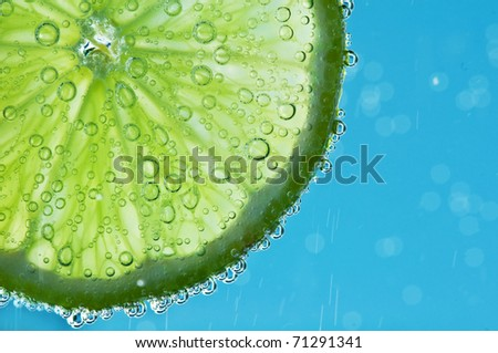 lime with bubbles on blue background
