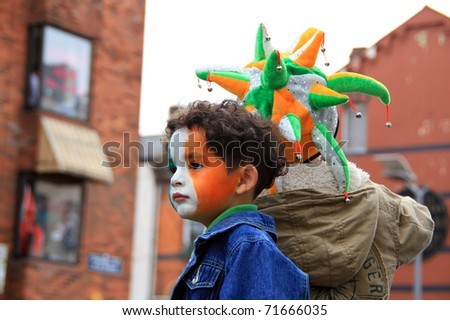 LIMERICK, IRELAND - MARCH 17: Unidentified child with a painted face in Irish colors participates in a parade for St. Patrick's Day on March 17, 2009 in Limerick, Ireland. It's a traditional Irish holiday parade. - stock photo
