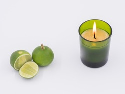 Limes and burning candle isolated on the white background
