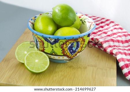 Limes in a colorful bowl on a wood cutting board with red and white dish cloth, white background