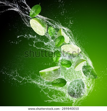 Limes with water splash isolated on dark background