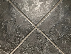 Limescale or soap scum on black tile in the bathroom