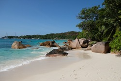Limestone boulders towering over white sand beaches fringed by lush green foliage, the Seychelles