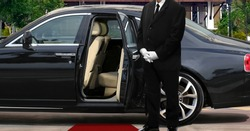 Limo driver standing next to opened car door with red carpet