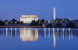 Lincoln Memorial and the Washington monument, DC landmarks, illuminated in the blue hour and reflecting in the water of the Potomac River.