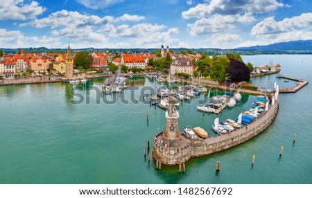 Lindau, Germany. Antique bavarian town at Lake Constance (Bodensee). Monument with statue of lion at entrance to port, yachts by piers. Summer landscape blue sky. #1482567692