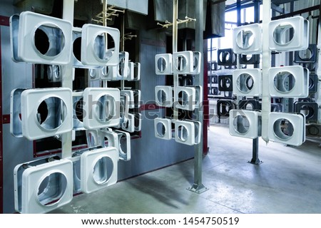 line for painting metal products in white color coating. Square metal products with a round hole hang on mounts after powder painting #1454750519