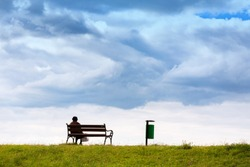 Line horizon and earth on a background of beautiful blue clouds. One woman sits on a bench and looks at the sea. Horizontal frame. Color photography