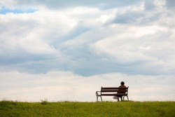 Line horizon and earth on the background of beautiful clouds. One woman sits on a bench and looks at the sea. Horizontal frame. Color photography