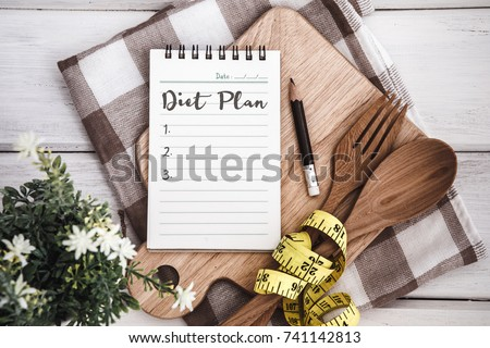 Line Notepad with Diet Plan list text  on chopping board with wooden fork and spoon and measuring tape on white table , recipes food or diet plan for healthy habits shot note background concept