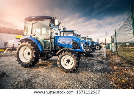 Line of blue tractors prepared for agricultural customers at dealership parking lot. Stock blue tractors prepared to be sold. #1571152567