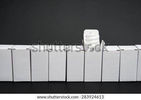 line of boxes with one open, an energy saving light bulb stands out
