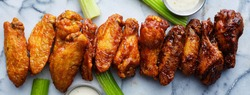 line of buffalo chicken wings drenched in different sauces