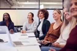 Line Of Businesswomen In Modern Office Listening To Presentation By Colleague
