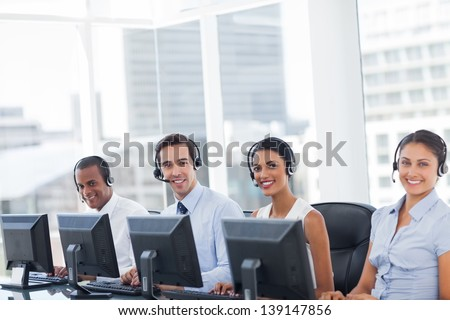Line of call centre employees smiling and working on computers