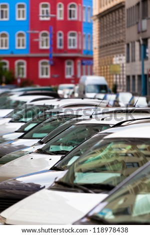 Line of Cars on the city street. Bright houses as a background