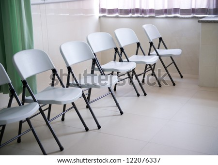 line of chairs in simple empty waiting room.