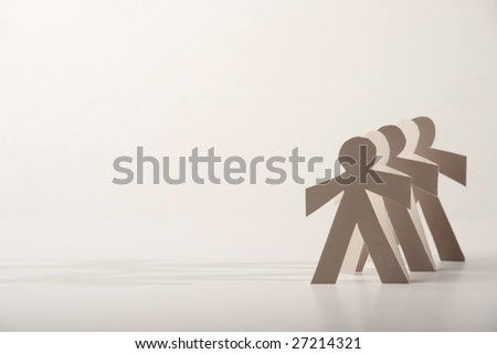 Line of cutout paper dolls throwing a shadow