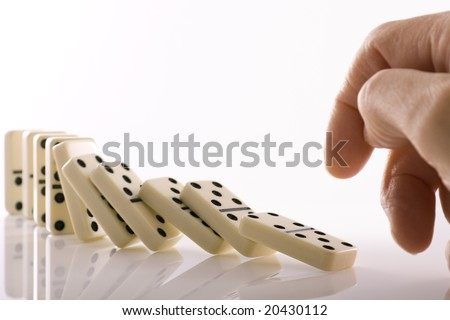 Line of dominos falling down after being pushed by finger
