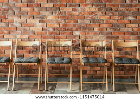 line of empty chairs on the brick wall loft background. vacant seat. concept of waiting area or job interview session. competition rivalry and promotion. #1151475014
