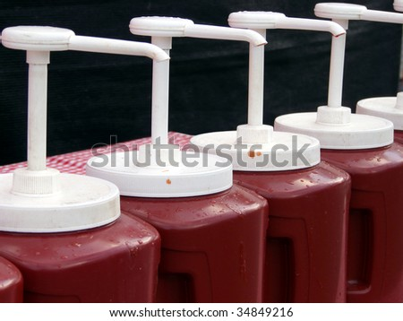 Line of jumbo size ketchup dispensers at a county fair